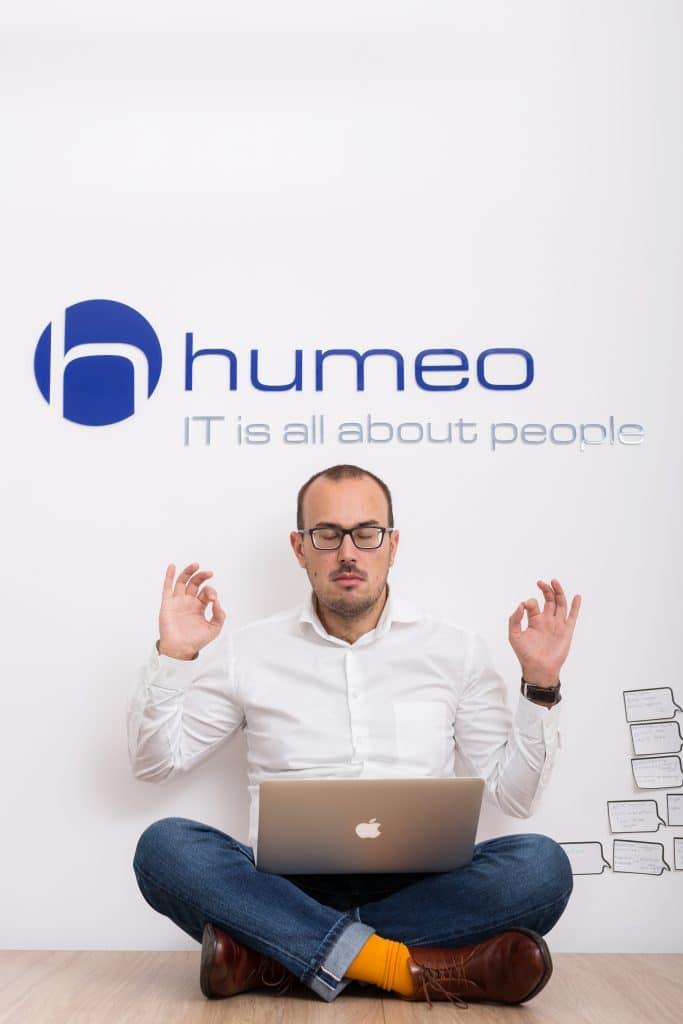 Powrót do biura po koronawirusie? Zrelaksowany i zadowolony szef firmy siedzący po turecku z laptopem na kolanach w biurze agencji rekrutacyjnej IT Humeo w Krakowie